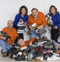 """George """"The Shoeman"""" Hutchings happily buried under a pile of shoes."""