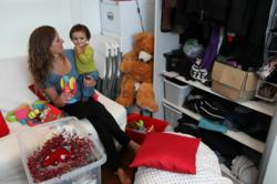 A young woman and baby are surrounded by boxes and other seasonal things that could be stored away using Storemates.co.uk