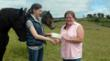 Alexandra Gritta, President of Charity Book Series®, Inc., presents a donation check to Jennifer Kunz, Duchess Sanctuary's Ranch Manager. A rescue horse named India appears to be giving Alexandra an encouraging nudge from behind. (Photo credit: Charity Book Series®, Inc.)