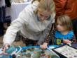 Mother and daughter lookng at Sea Glass Journal's booth display