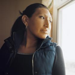 Lakota Sioux woman looks out window hoping for her children.