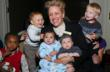 •Several Sources Founder, Kathy DiFiore at the 30th Anniversary Celebration of the Several Sources Shelters surrounded by current Several Sources babies from left to right Julian, Viktor, Jordany, Al