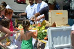 Sidekim Foods serves children fresh fruits and vegetables at their Kickoff BBQ this past July.