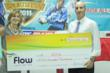 Michele English (L) President & COO of Flow presents a donation to Brian Horvath, Principal of the American International School in Kingston (AISK) to host the SportsFeva Invitational Tournament on Tuesday, November 1, 2011