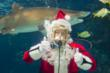 Scuba Santa greets visitors to Newport Aquarium from within the shark tank.