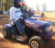 A lawn mower racer at the Sam Rogers US All American Open gets ready to mow with his Wheelies tractor wheel covers.