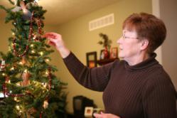 senior decorating Christmas tree
