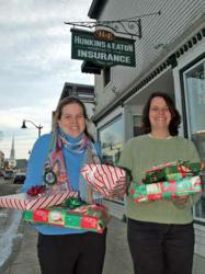 Anita Sjolander, left, and Heather Glover of Hunkins & Eaton in Littleton wrap up a holiday tradition helping Catholic Charities fill the lists of children in the local area