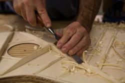 Luthier Jay Lichty carving the bracing of an acoustic guitar