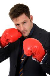 Businessman in suit wearing boxing gloves and fighting wrinkles with Knockout skincare for men.