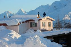 Residents dig out a second story roof as Valdez receives record early season snowfall prompting H2o Guides to offer heliskiing value package to snow-deprived Lower 48