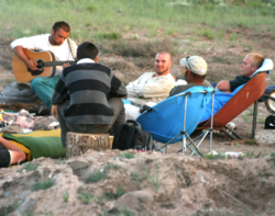Young adult men around a campfire outdoors during recovery at San Cristobal.