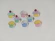 picture of decorated cupcakes pink green yellow blue on a white background