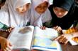 Students at a community learning center in Jakarta pore over a brand-new textbook provided by Books for Asia.