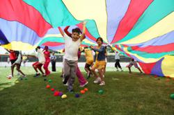 Kids playing parachute games at a field day activity.