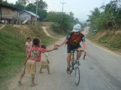 Friendly children and cyclist in Laos