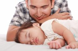 Dad watching baby sleep