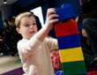 Boy playing with large LEGO(R) bricks.