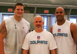 Coach Storms (middle) pictured with two Miami Dolphins