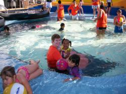AotS staff member and child playing in the pool