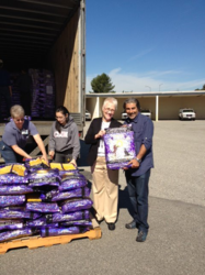 Friends of LA Animal Services' board president helps unload the truck from Solid Gold.