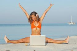 Girl on beach with laptop, smiling.