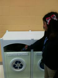 Girl using Max-R recycling bin.
