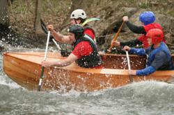 New Energy Works timberframers teamed up to battle the rapids in a custom crafted canoe during the Wild Water Derby. Photo © David Spier