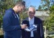 Hillsides CEO Joe Costa looks on as Dodger James Loney autographs his baseball cleats to donate for Hillsides Foster Soles.
