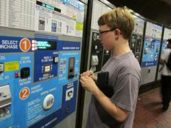 Teenage boy using DC Metro fare machine.