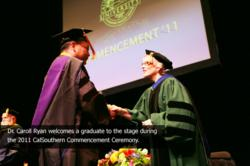 Dr. Caroll Ryan welcomes a graduate to the stage during the 2011 CalSouthern Commencement Ceremony.