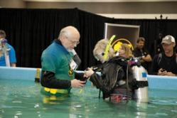 George Barron, volunteer at the Dive & Travel Expo held in Tacoma, WA April 21 & 22, 2012, helps a kid try scuba diving!