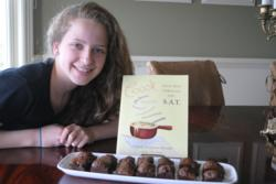 """Photo of Charis Freiman-Mendel with her cookbook, """"Cook Your Way Through The S.A.T.' and a plate of zucchini brownies, a recipe from the book."""