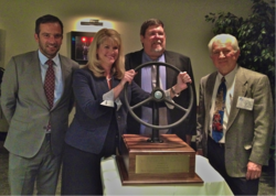 Laura Toole, Manager, Communications GM Northeast Region, takes the wheel of the 2012 POV of the Year Award. Left to right: GM Northeast Fleet Manager Pierre Kanter, Laura Toole, NEMPA President Keith Griffin and WheelsTV CEO Jim Barisano.