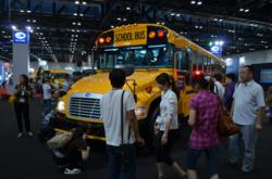 Chinese citizens view a Blue Bird school bus