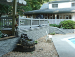 Faux stone wall siding is a great landscaping choice for around a pool-facing deck