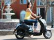 Beautiful girl riding a Vespa wearing a designer athletic fashion top.