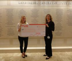 Monica Belling from Small Army for a Cause presents a check for $32,000 to Amy Cronin of the Dana Farber Cancer Institute
