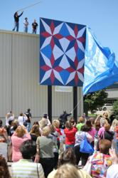 Hundreds of quilters watch at AccuQuilt's new Omaha Headquarters as the winning Barn Quilt Block design is unveiled.