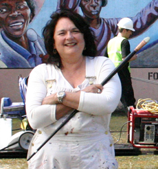 Judy Baca,a world-renowned painter and muralist, holding a larger mural brush in fron of a mural