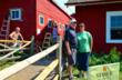 Stanek salesman Mike McMillan and Renee Schapel, Parma Area Historical Society Trustee stand in front of the farm's buildings as volunteers install the new windows behind them.