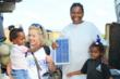 Resident of San Mateo recieving her solar lamp