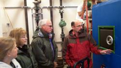 Three federal government officials being briefed on the new biomass boiler system installed at two federal buildings in Ketchikan, Alaska, in 2011.