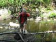 Hiker crosses a stream on Maine's Appalachian Trail.