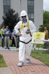 Andy Kulik models a Tyvek® suit, half-face air purifying respirator, fall protection harness, hard hat, hearing protection, and 4 gas meter.