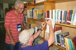 IE Executive Director Steve Cox reviews the children's collection with librarian Adrian Guerra at a Havana public library.