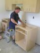 "Marking a milestone, a Habitat for Humanity volunteer works on the 100th installation for ""Cabinets for Humanity,"" made with PureBond® hardwood plywood from Columbia Forest Products."