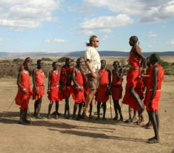 A traveller takes part in a traditional Maasai warriors dance with the Maasai