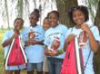 Kids showing off their new water bottles and draw string bags