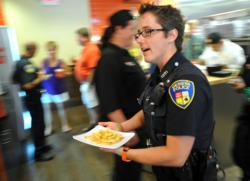 Geneva Police Officer Penny Boedigheimer carries an order of French fries to a Tom & Eddie's customer at last year's Burgers & Badges.